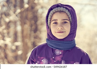 Cute young girl in winter clothes with beautiful bokeh background