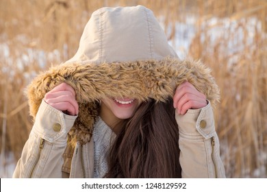Cute young girl at winter landscape hiding his face under hood, outdoors