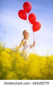 Cute young girl in yellow field having fun with red balloons