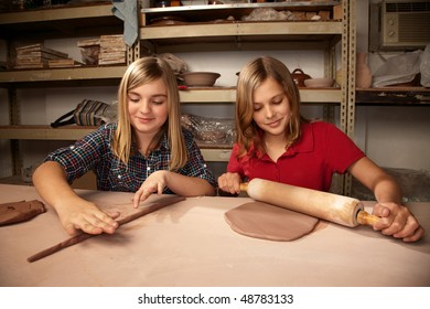 Cute young girls working on projects in a clay studio