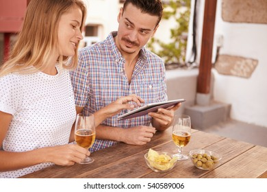 Cute young guy looking inquisitively at pretty blond girl who is looking and pointing at his touchpad with beers and snacks