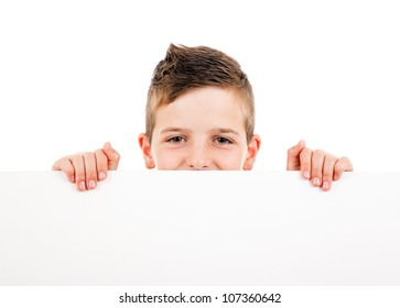 Cute young happy boy holding a blank board against white background