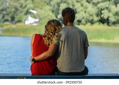 Cute young and happy couple sitting on the bench hugging on river background