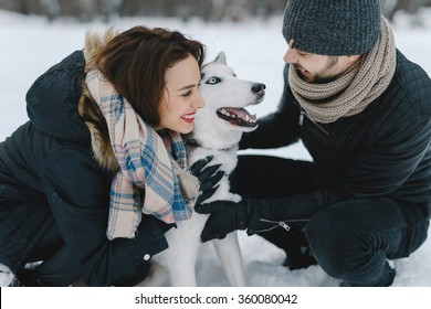 Cute young hipster couple having fun in winter park with their friend husky dog on a bright day hugging each other and smiling
