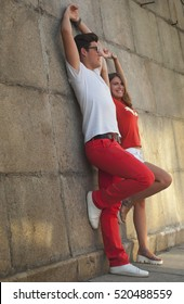 Cute young hipster couple having fun and smiling near the wall on a bright summer day