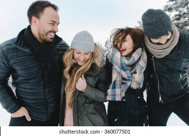 Cute young hipster couples walking in the snow having fun in winter park on a bright day hugging each other and smiling