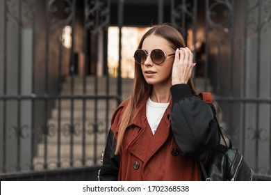 Cute young hipster woman in fashion sunglasses in stylish trench coat with leather black backpack straightens hair near old iron gate on street. European girl model posing in trendy clothes outdoors.