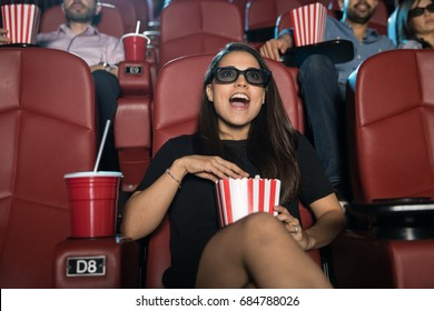 Cute young Hispanic woman looking surprised and excited at the movie theater while watching a 3d film