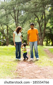 cute young indian couple with baby boy walking outdoors