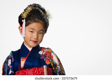 A cute young Japanese girl wearing a Kimono on a white background.