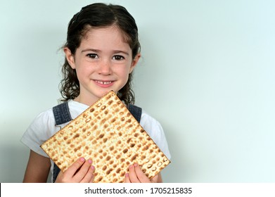 Cute young Jewish girl (age 06) holding Matzo bread on Passover Jewish holiday looking at camera. Real people. Copy space
