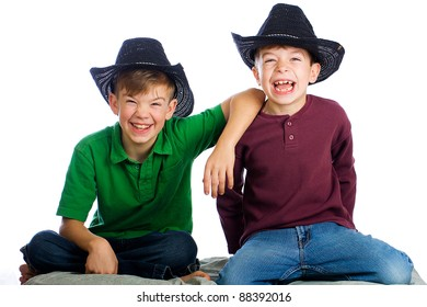 Cute young kids with happy smiles wearing cowboy hats.