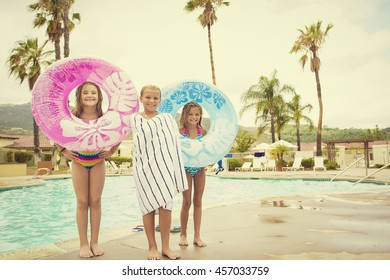 Cute young kids playing in the pool on a summer day. Warm tinted image