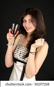 Cute young lady with glass of red wine over black background