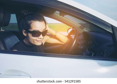 Cute young lady happy driving car