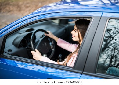 Cute young lady happy driving car on road