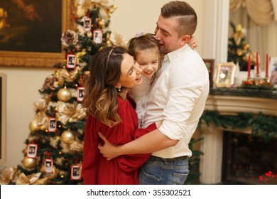 Cute young laughing family at home near the christmas tree in decorated room
