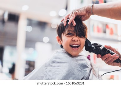 Cute young little boy getting a haircut at salon