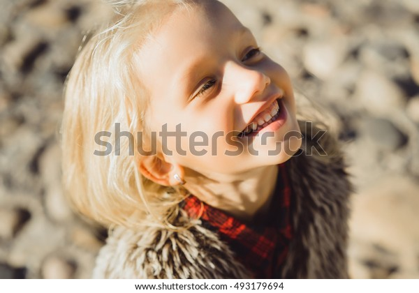 Cute and young little girl smiling. Outdoor portrait of cute little girl in summer day.