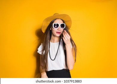 cute young long-haired girl model in fashionable big hat and sunglasses posing on yellow background