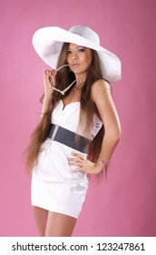 Cute young long-haired woman in the white dress and a big hat posing in studio
