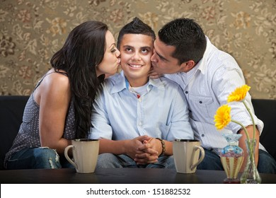 Cute young man being kissed by parents