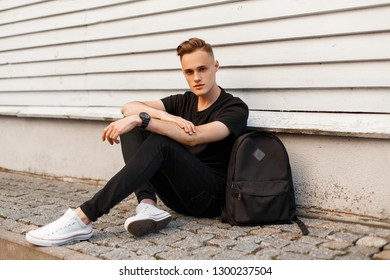 Cute young man in a black T-shirt in stylish black jeans in trendy sneakers with a black sports backpack is resting sitting on the asphalt near a white wooden vintage building. Stylish guy.