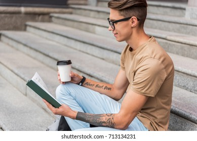 Cute young man studying on steps near university building