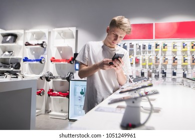 A cute young man in a white T-shirt chooses a smartphone in the electronics store. A student buys a phone in the store. Buy a smartphone in the tech store