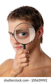 Cute young man without a shirt looking through a magnifying glass