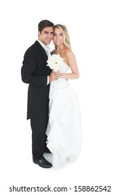 Cute young married couple posing holding a white bouquet smiling at camera