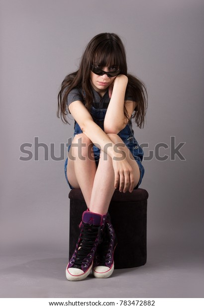 Cute Young Millennial Woman in Overalls and Cute Shoes Sitting on Velvet Stool