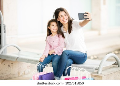 Cute young mother and daughter sitting outdoors of a shopping mall and taking a selfie with mobile phone