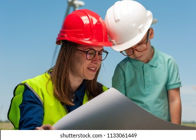 Cute young mother engineer in a red helmet and glasses shows her engineering plan to her talented little son