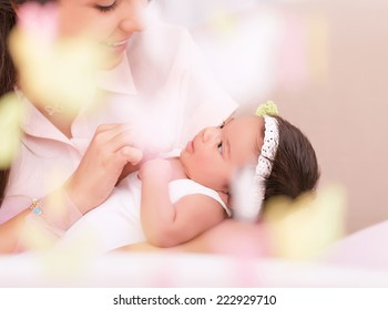 Cute young mother looking on sweet newborn daughter, take care about her, photo with soft focus, happy motherhood concept