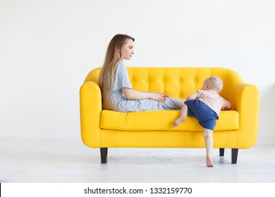 Cute young mother sits on a yellow sofa in a blue dress and communicates with her little two-year-old son. Concept of decree and child care. Copyspace