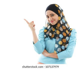Cute young Muslim woman pointing on empty space, isolated on white