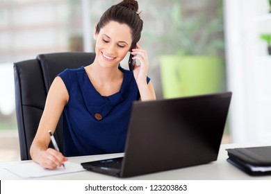 cute young office worker talking on cell phone in office