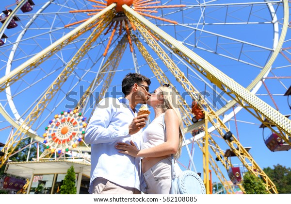 Cute young people, newlyweds kissing, hugging and smiling, looking into eyes of each other and posing for photos, guy holding ice cream on background of large and colorful ferris wheel at an amusement