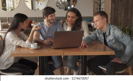 Cute young people pointing their forefingers on laptop screen. Long shot of multirace group of friends entertaining with portable computer at the cafe. Two handsome guys and two pretty girls sitting