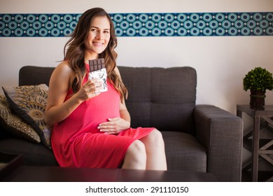 Cute young pregnant woman craving a bar of chocolate and smiling