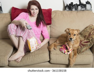 Cute young red-haired woman in pink pajamas sitting in living room eating popcorn with her adorable dog next to her on couch - watching tv
