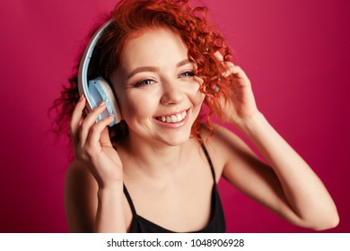 cute young redhead girl in big headphones happy smiling. close up portrait in Studio on red background