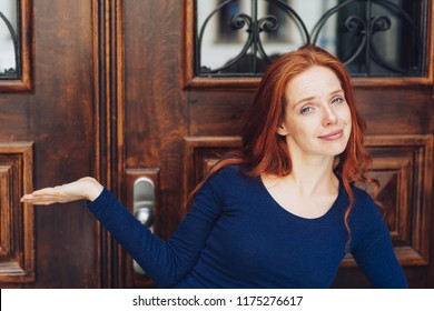 Cute young redhead woman holding out an empty palm as she stands in fron of a large old wood and glass door smiling at the camera