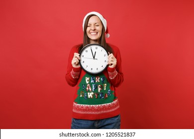 Cute young Santa girl in Christmas hat hold round clock, keeping eyes closed isolated on red background. Time is running out. Happy New Year 2019 celebration holiday party concept. Mock up copy space