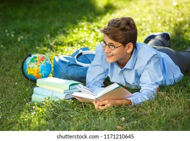cute, young schoolboy in round glasses and blue shirt lies on the grass and holds a book in his hands, reads in the park. Education, back to school concept