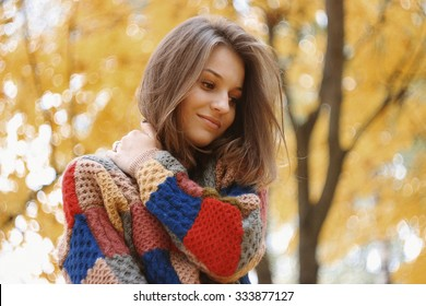 Cute young smiley dreaming woman with beautiful face and hair in autumn forest.Yellow background