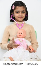 Cute young smiling/happy Indian girl/kid playing with doctor set examining patient baby doll, Kerala India . Asian child/beautiful daughter with her toys plays hospital/clinic with her medical tools.