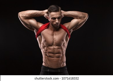 Cute young sports man in red t-shirt shows relief abdominal muscles in gym