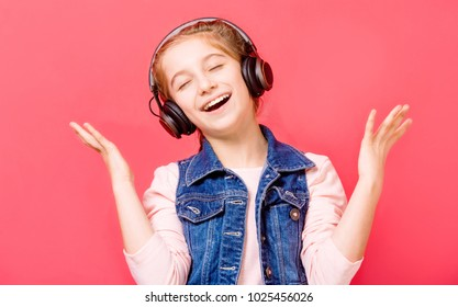 Cute young teen girl enjoying listening to music in wireless headset over rose background